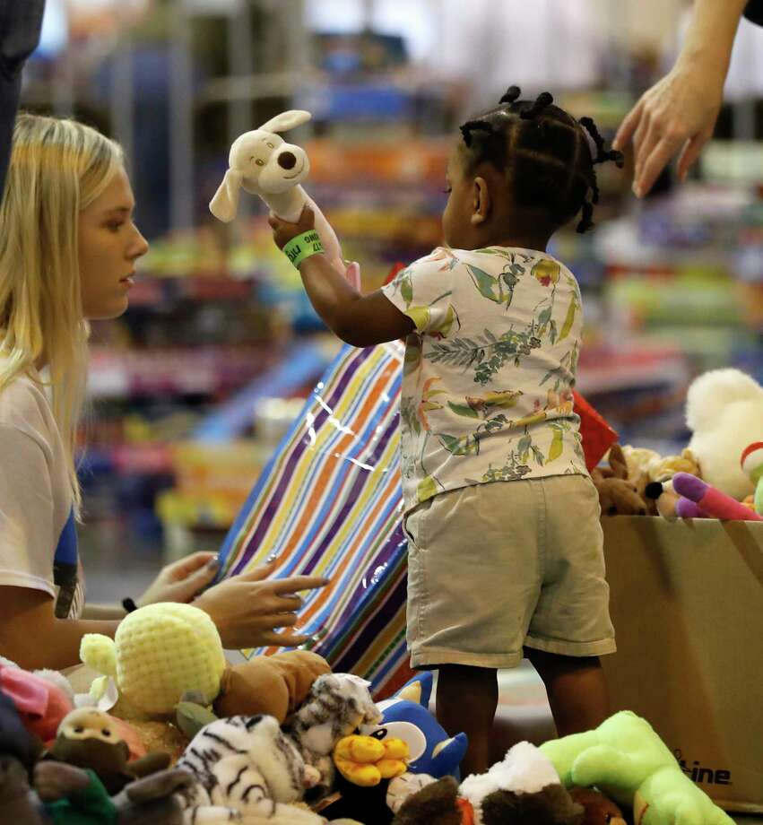 Kate Wimberley, 17, plays with Emani Watkins, 1, in NRG Center, where the goods, toys, snacks and clothing where being distributed for the 2500 people sheltering there, who were affected by Tropical Storm Harvey, Wednesday, Aug. 30, 2017, in Houston.  ( Karen Warren / Houston Chronicle ) Photo: Karen Warren, Staff Photographer / @ 2017 Houston Chronicle