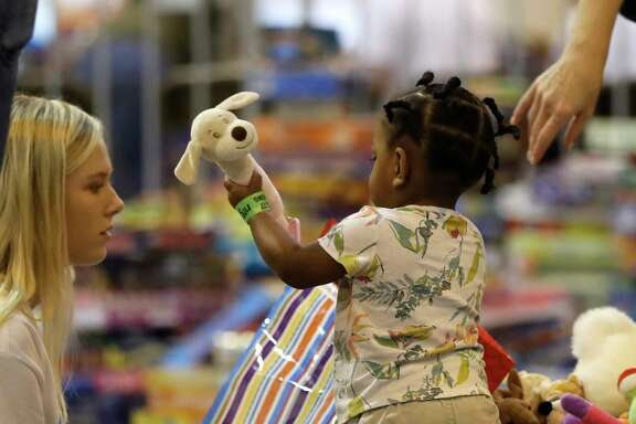 Kate Wimberley, 17, plays with Emani Watkins, 1, in NRG Center, where the goods, toys, snacks and clothing where being distributed for the 2500 people sheltering there, who were affected by Tropical Storm Harvey, Wednesday, Aug. 30, 2017, in Houston.  ( Karen Warren / Houston Chronicle )