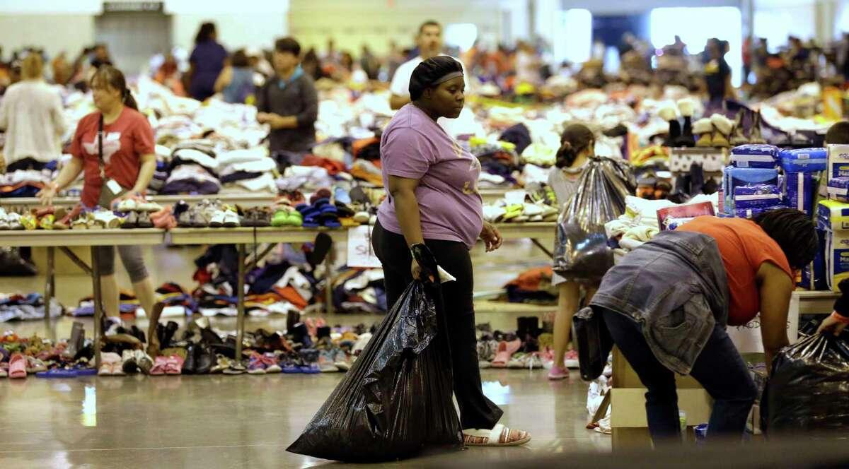 Hurricane Harvey flood evacuees look through supplies at a shelter set up inside NRG Center.