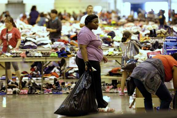 Hurricane Harvey flood evacuees look through supplies at a shelter set up inside NRG Center.