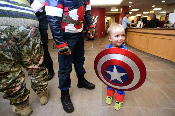 Ronan Farrell, 2, of Guilford borrows a shield from Captain America during Guilford Comic Con at the Guilford Free Library on October 21, 2017.