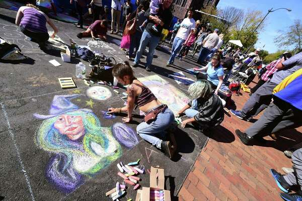 Sara Hope Hill, a.k.a. the Goblin Queen, of New Haven works on a witch drawing during the New Haven Chalk Art Festival on the Broadway Island in New Haven on October 21, 2017.