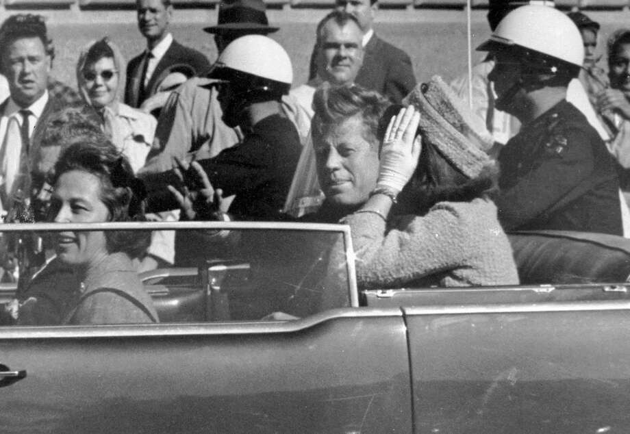 President John F. Kennedy, next to first lady Jacqueline Ken ne dy, waves from his Dallas motorcade before his assassination. Photo: Jim Altgens, Associated Press