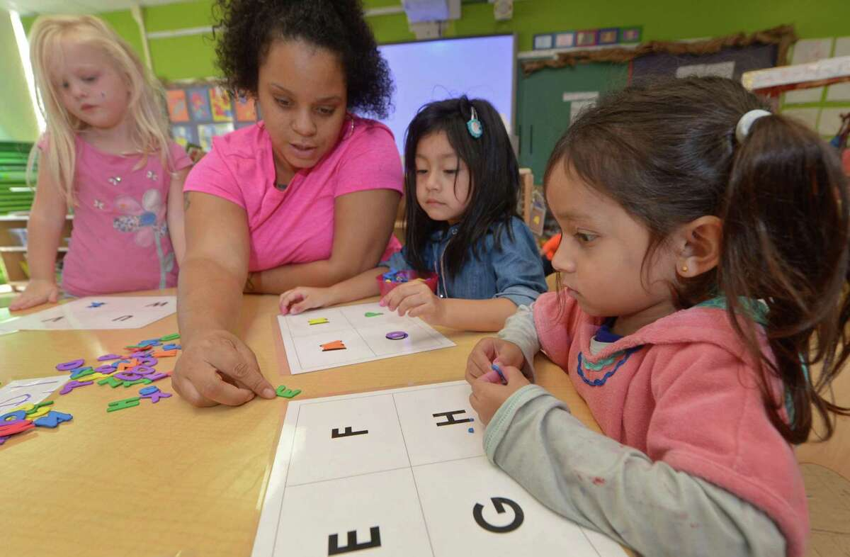 Preschoolers Thora Johansen, Camila Silva and Afeefah Saiyed get help from their teacher, Jaclyn Price, while working on a word puzzle during their ELLI class at Fox Run Elementary School Thursday, Oct. 18, in Norwalk. Norwalk Public Schools made waves when the Board of Education voted to implement the Early Language and Literacy Initiative (ELLI) curriculum in all of its preschools in accordance with Superintendent Steven Adamowskis Strategic Operating Plan for closing the achievement gap. The ELLI program was developed by Stepping Stones Museum for Children and Literacy How.
