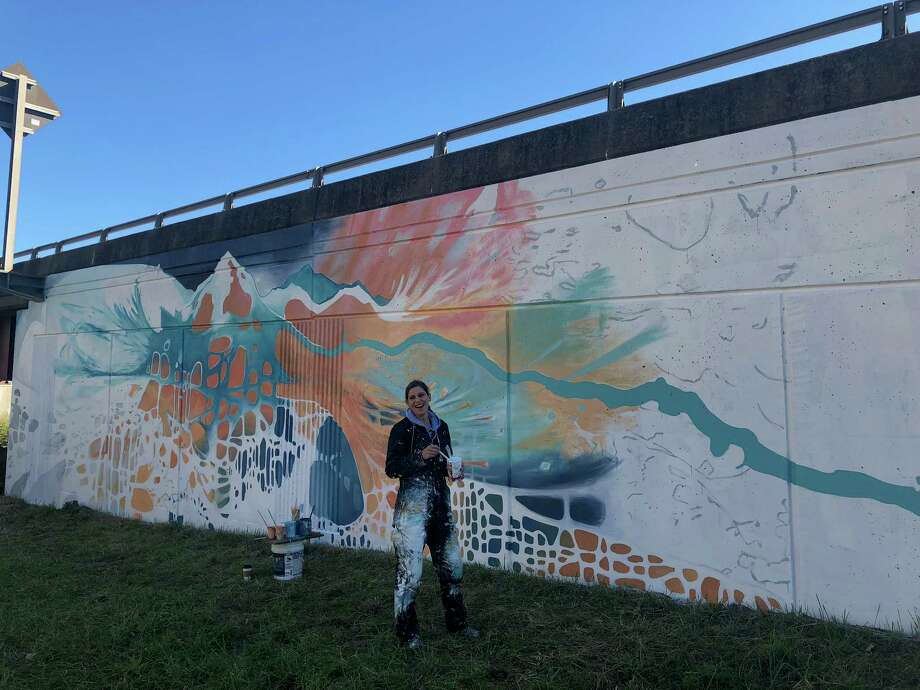 "Rachel Baxter works on her mural, ""The River That Flows in Two Directions"", on the retaining wall of the I-787 at Columbia and Water streets. Her mural, which depicts the Adirondack Mountains and Hudson River, is one of three new additions to the Albany Parking Authority and Albany Central Gallery's beautification project for downtown Albany. Photo: (Massarah Mikati/Times Union)"