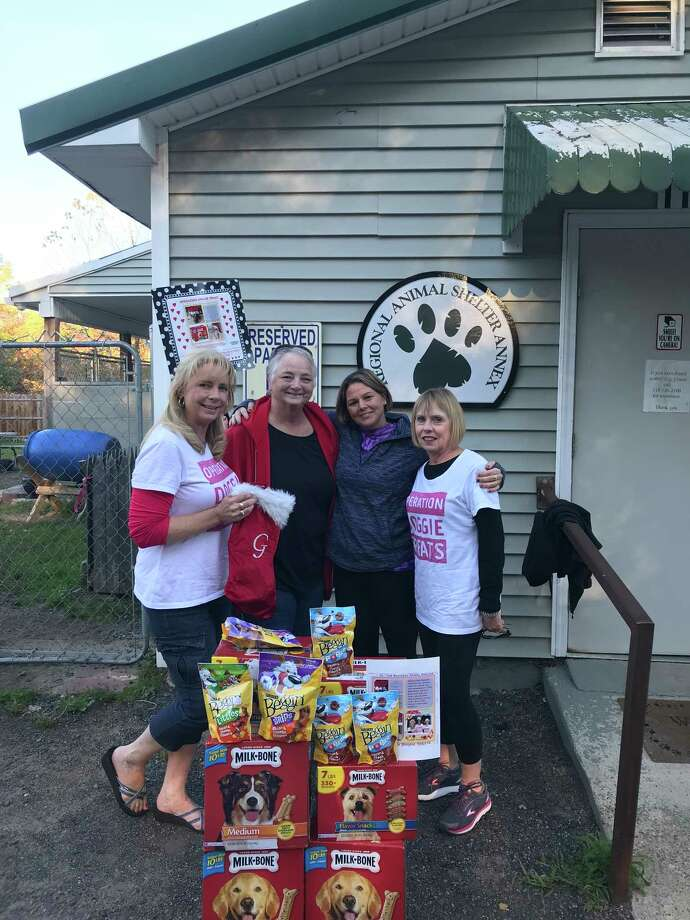 Judles Mulrooney of Operation Doggie Treats Inc., Mary Pressman and volunteers at the animal shelter in Gloversville stand with some of 50 pounds of goodies delivered by the organization Wednesday, Oct. 18, 2017. The group ios just finishing the process of become a 501c3 charity. A total of 1,700 pounds has been brought to shelters over the last 10 months. Mulrooney started the deliveries in memory of her dog, Gunner.(Judles Mulrooney)