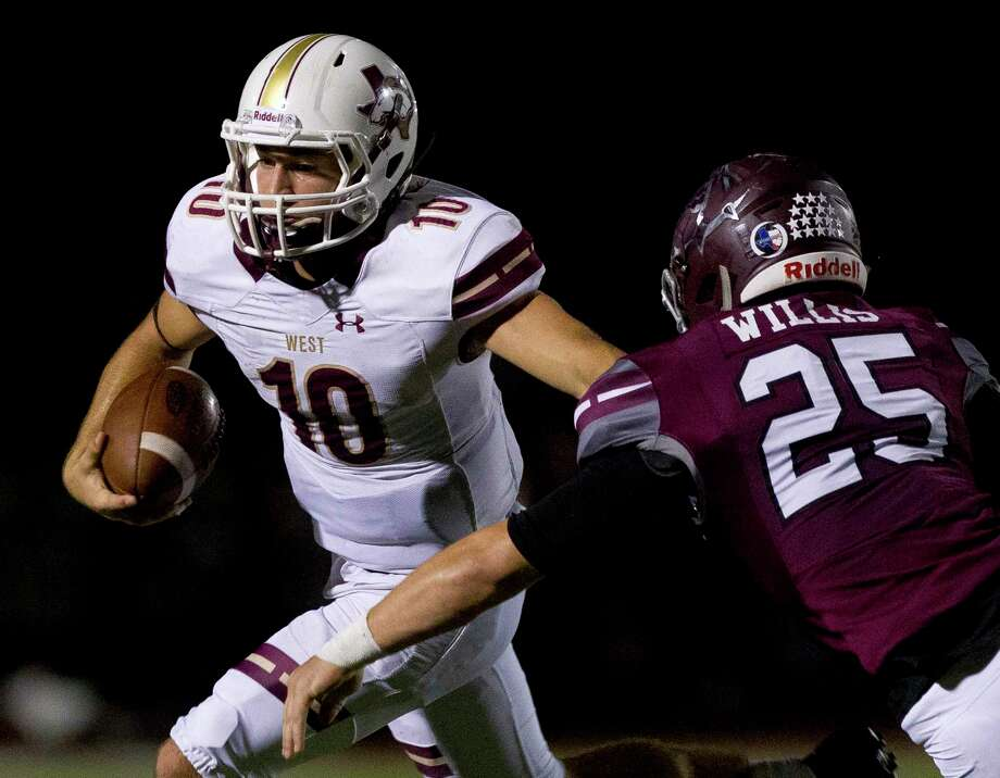 Magnolia West quarterback John Matocha (10) runs past Magnolia inside linebacker Bo Willis (25) during the second quarter of a District 20-5A high school football game, Friday Oct. 20, 2017, in Magnolia. Photo: Jason Fochtman, Staff Photographer / © 2017 Houston Chronicle
