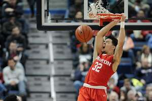 Houston's Rob Gray reacts while dunking the ball as Connecticut's Kentan Facey, left, looks on, in the first half of an NCAA college basketball game, Wednesday, Dec. 28, 2016, in Hartford, Conn. (AP Photo/Jessica Hill)