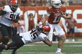 Longhorn quarterback Sam Ehlinger yanks Chad Whitener away from a tackle at midfield as UT plays Oklahoma State University at DKR Stadium on October 21, 2017.