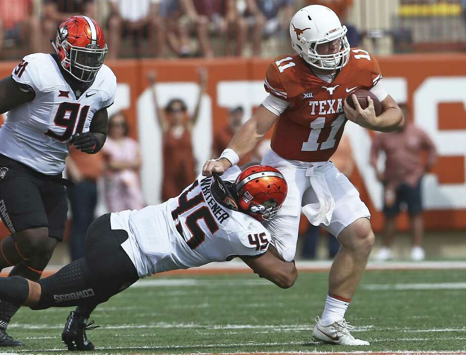 Longhorn quarterback Sam Ehlinger yanks Chad Whitener away from a tackle at midfield as UT plays Oklahoma State University at DKR Stadium on October 21, 2017. Photo: Tom Reel, Staff / San Antonio Express-News / 2017 SAN ANTONIO EXPRESS-NEWS