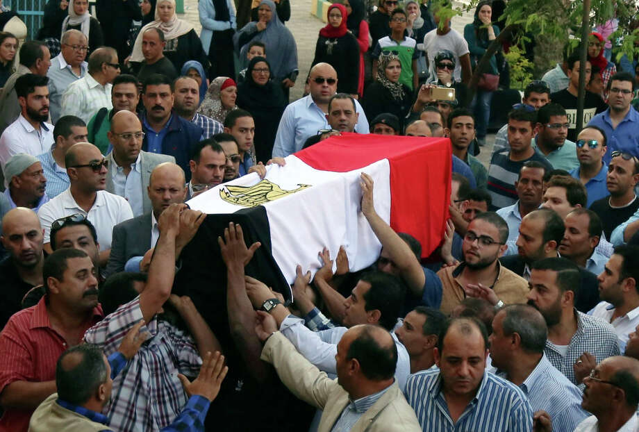 People carry on Saturday the coffin of police captain Ahmed Fayez, who was killed in a raid about 84 miles southwest of Cairo. The raid could be the deadliest attack by militants on Egypt's security forces. Photo: Alaa Elkassas, STF / Amr Nabil