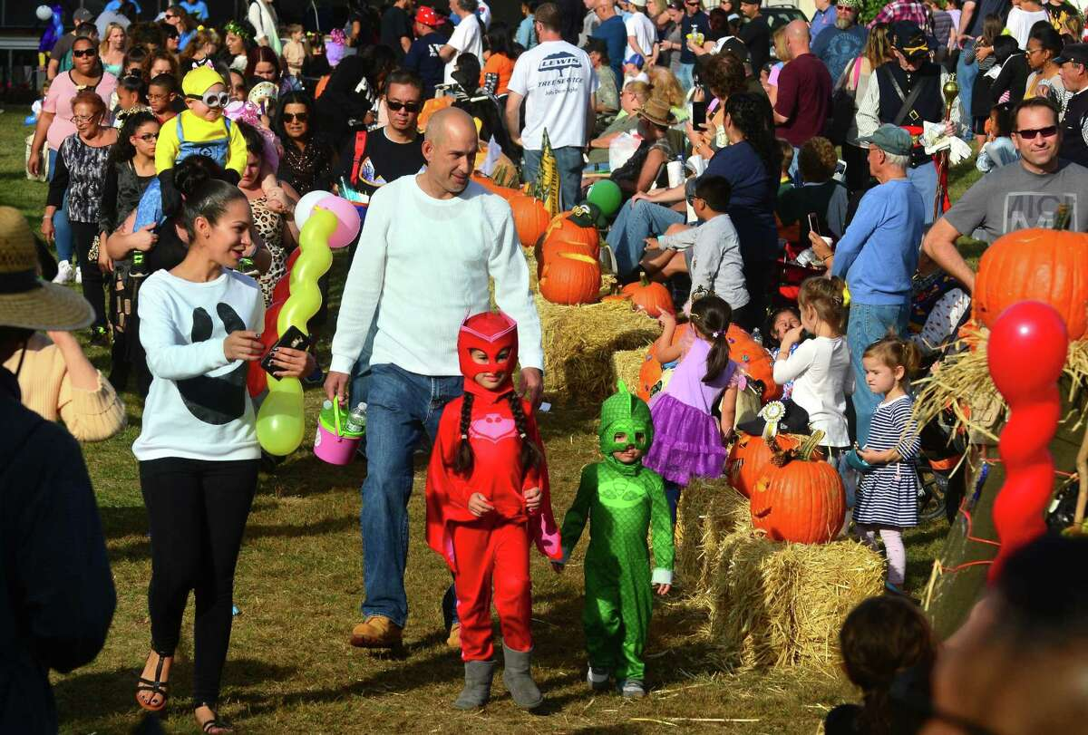 Victoria Rosa, 6, of Milford, and her little brother Pedro, 2, and their parents Crystal and Pedro Sr., take part in the children's costume parade during the annual Great Pumpkin Festival held at Boothe Memorial Park in Stratford, Conn. on Saturday Oct. 21, 2017. In addition to the costume parade, the festival included a pumpkin carving contest with prizes, DJ music, games, crafts, face painting, refreshments, a pie baking contest, a scarecrow judging contest, horse-drawn hayrides, the roaming railroad, and tours through the various historic buildings at the park, including tours of the Model Train Museum and Observatory. Bunnell High School STAGE theater group performed skits and costumed actors from the Players at Putney Gardens strolled the grounds. New to the festival this year was a Falconer Show and Live Animal Experience.