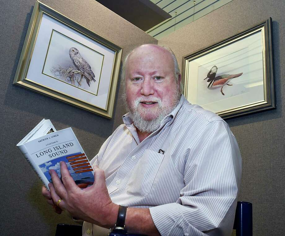 "Author, designer, illustrator and photographer, Patrick J.  Lynch, of North Haven, at an exhibit of illustrations from his recent book, ""A Field Guide to Long Island Sound,"" at the Ives Gallery at the New Haven Free Public Library on Tuesday. The exhibit continues through Dec. 2. Photo: Catherine Avalone / Hearst Connecticut Media / New Haven Register"