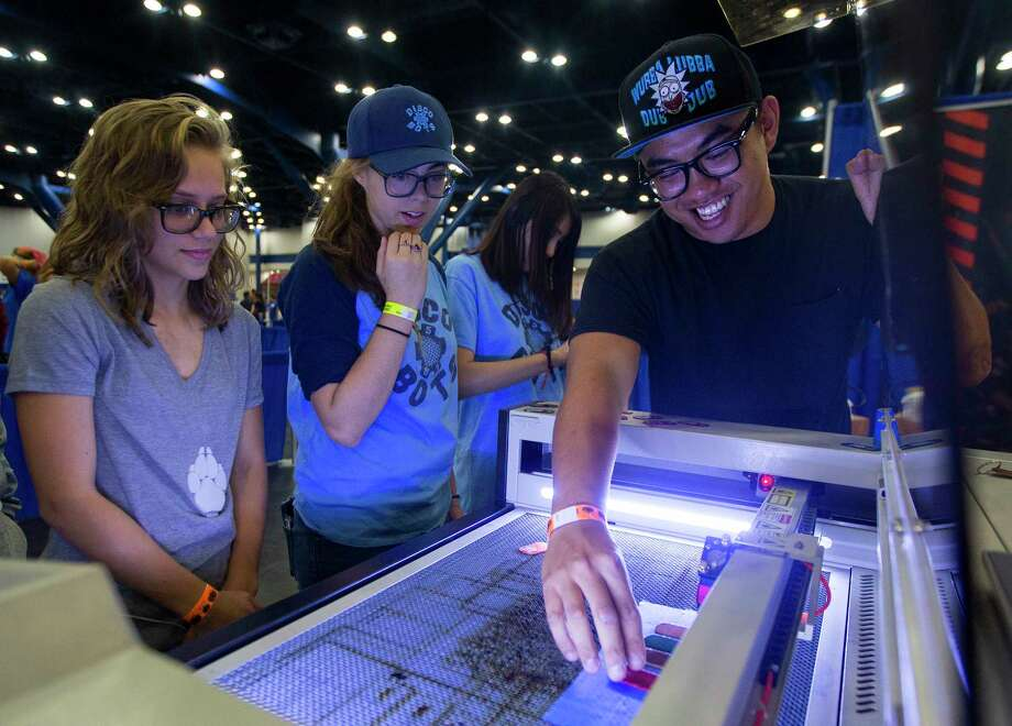 Anderson Ta, right, makes souvenir keychains with a laser cutter while promoting TXRX Labs during the Maker Faire at George R. Brown convention center on Saturday. Photo: Annie Mulligan, Freelance / @ 2017 Annie Mulligan