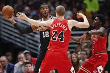 San Antonio     Spurs     forward LaMarcus Aldridge (12) looks to pass the ball against Chicago Bulls forward Lauri Markkanen (24) and guard Justin Holiday (7) during the first half of an NBA basketball game, Saturday, Oct. 21, 2017, in Chicago. (AP Photo/Kamil Krzaczynski)