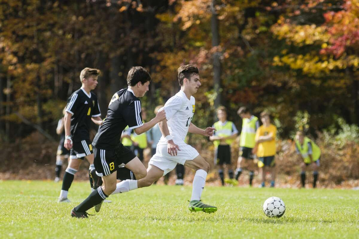 Dow junior Max Sanchez takes the ball down the field as Traverse City junior Joseph Aulicino (8) and senior Wiley Fraser (11) play defense during the district championship at H.H. Dow High School in Midland on Saturday, Oct. 21, 2017. Dow beat Traverse City Central 1-0. (Danielle McGrew Tenbusch/for the Daily News)