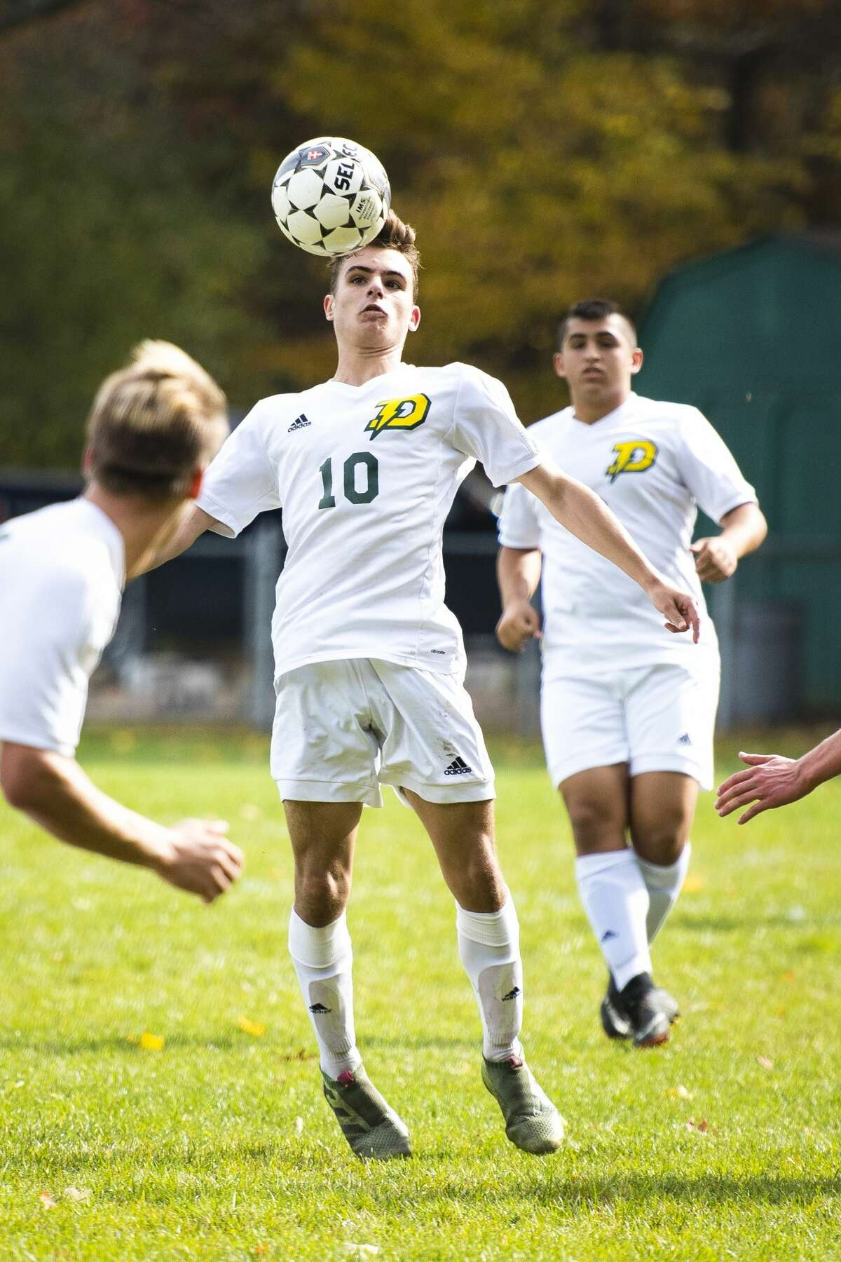 Dow senior Cody Glazier chest-bumps the ball as teammate, junior Adam Elfawal, runs behind himduring the district championship at H.H. Dow High School in Midland on Saturday, Oct. 21, 2017. Dow beat Traverse City Central 1-0. (Danielle McGrew Tenbusch/for the Daily News)