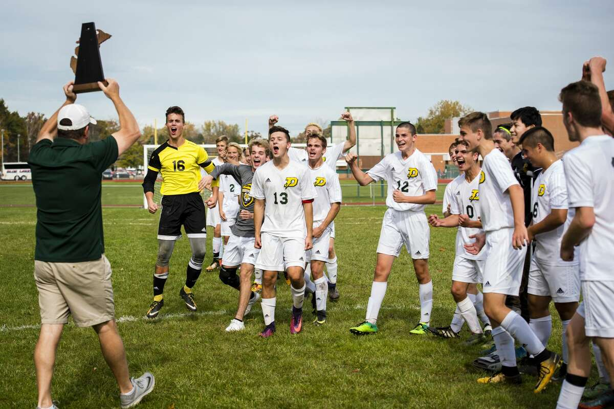 Coach Tom McDaniel carries the district championship trophy to the Dow Chargers after they beat Traverse City Central 1-0 at H.H. Dow High School on Saturday, Oct. 21, 2017. Dow beat Traverse City Central 1-0. (Danielle McGrew Tenbusch/for the Daily News)