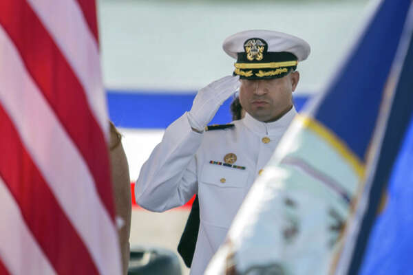 Commanding officer of the Virginia-class submarine USS Washington Cmdr. Gabriel Cavazos salutes during the presentation of the colors at the beginning of the commissioning ceremony at Naval Station Norfolk Saturday, Oct. 7, 2017.