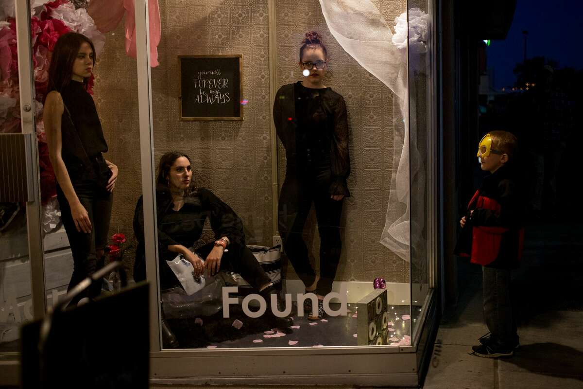 Students pose as a boy watches them during the annual Mannequin Night on Oct. 19, 2017. (Samantha Madar/for the Midland Daily News)