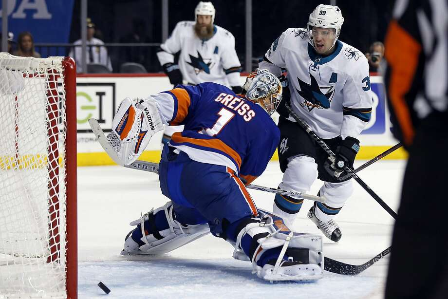 The Sharks' Logan Couture (right) scores his third goal of the game past Islanders goalie Thomas Greiss in the third period Saturday. Despite Couture's onslaught, poor defensive play hurt San Jose. Photo: Adam Hunger, Associated Press
