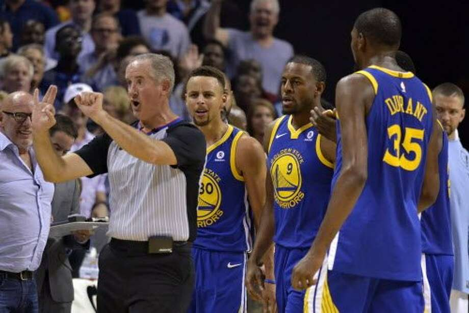 Referee Scott Wall, left, calls Golden State Warriors guard Stephen Curry (30) for a foul as Curry and Warriors forwards Andre Iguodala (9), and Kevin Durant (35) react during the second half of an NBA basketball game Saturday, Oct. 21, 2017, in Memphis, Tenn. Curry and Durant were ejected after arguing with Wall over the call. (AP Photo/Brandon Dill) Photo: Brandon Dill, Associated Press