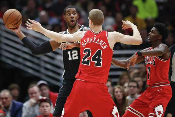 Spurs forward LaMarcus Aldridge (12) looks to pass the ball against Bulls forward Lauri Markkanen (24) and guard Justin Holiday (7) during the first half on Saturday, Oct. 21, 2017, in Chicago.