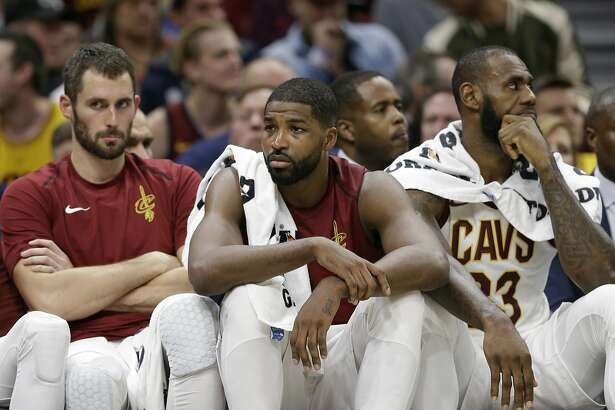 Cleveland Cavaliers' Kevin Love, left to right, Tristan Thompson and LeBron James sit on the bench in the second half of an NBA basketball game against the Orlando Magic, Saturday, Oct. 21, 2017, in Cleveland. (AP Photo/Tony Dejak)