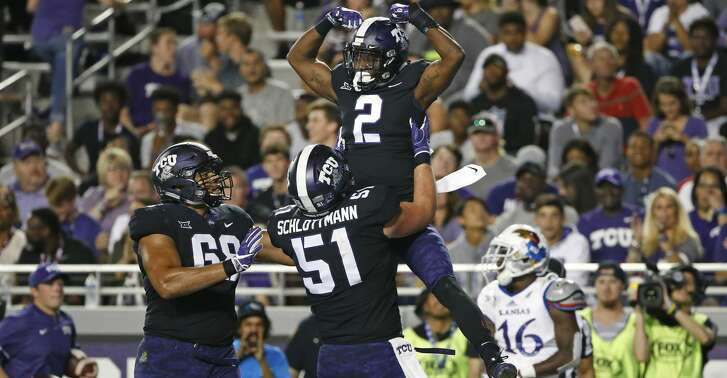 TCU wide receiver Taj Williams (2) and teammates Austin Schlottmann (51) and Joseph Noteboom (68) celebrate Williams' touchdown catch as Kansas cornerback Kyle Mayberry (16) looks away during the second half of an NCAA college football game Saturday, Oct. 21, 2017, in Fort Worth, Texas. TCU won 43-0. (AP Photo/Ron Jenkins)