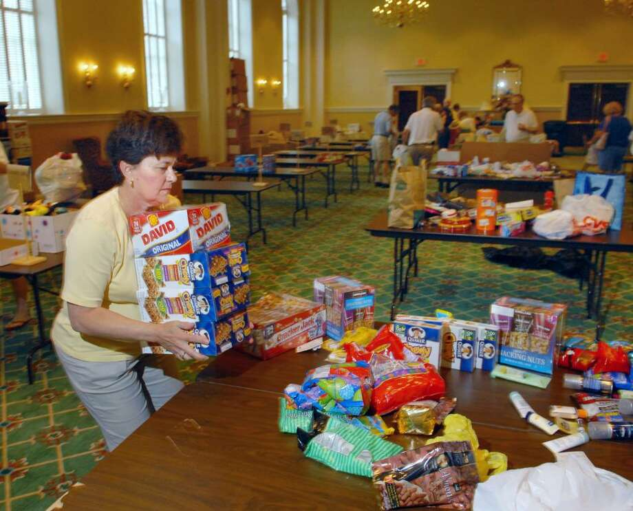 Volunteer Claudette Greene of Greenwich stacks dry goods in the First Presbyterian Church Hall, Greenwich, Friday afternoon, June 25, 2010.  Greene and other volunteers were collecting items, which will be shipped  to soldiers serving in Afghanistan. Photo: Bob Luckey / Greenwich Time
