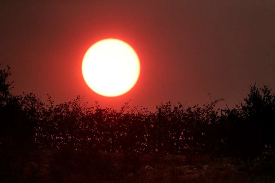 The sun, turned red from smoke in the area, sets behind a vineyard on Lovall Valley Road as the Partrick Fire continued to burn slowly east of Sonoma, Calif., on Thursday, October 12, 2017. Hot weather is returning to the Bay Area this week.