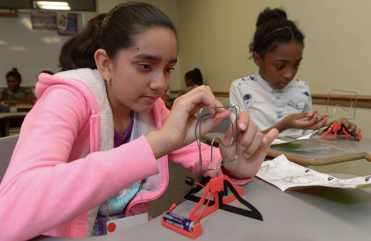 Kimberly Corona, 11, and Naila Dacres, 10, build electrical circuits at the Amazing Girls Science Conference Saturday, October 21, 2017, at Norwalk Community College in Norwalk, Conn. Girls in the fourth through eighth grades get the chance to build series and parallel circuits that can light a bulb and sound a buzzer.The workshop is organized by Amazing Girls, an initiative to teach young girls that science is fun.