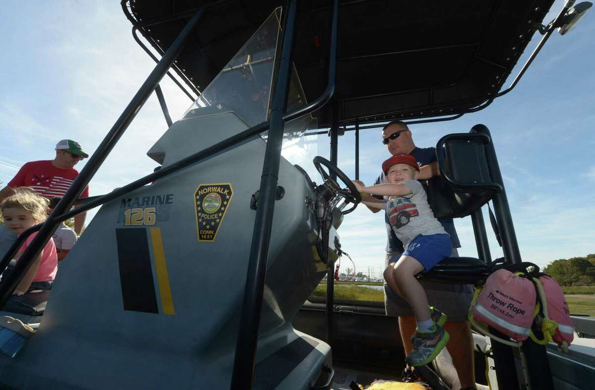 Sean Dolyak and his son Chase Dolyak, 3, sit in a Norwalk Marine Police Boat during The Human Services Council's annual KidzFest Saturday, October 21, 2017, at Taylor Farm Park on Calf Pasture Beach Road in Norwalk, Conn.