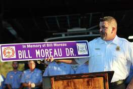 """David Rodgers, assistant chief for Dayton VFD, holds up a sign naming the road leading into the fire department's new station on SH 321 as Bill Moreau Drive. Moreau was a former fire chief. The new fire station was named in honor of W.E. """"Bill"""" Burnett, who was fire chief from 1976 to 1988 and dedicated 23 years of his life to the department."""