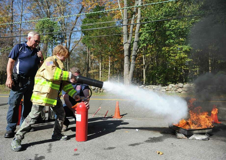 Greenwich's Gavin Haroche, 11, uses a fire extinguisher to put out a blaze at the Round Hill Volunteer Fire Company's annual open house at the station in Greenwich, Conn. Sunday, Oct. 22, 2017. Children and parents got to meet the firefighters and go for a ride in a fire truck and try on gear. Firefighters also gave a live demonstration how to use a fire extinguisher to put out a house fire. Photo: Tyler Sizemore / Hearst Connecticut Media / Greenwich Time
