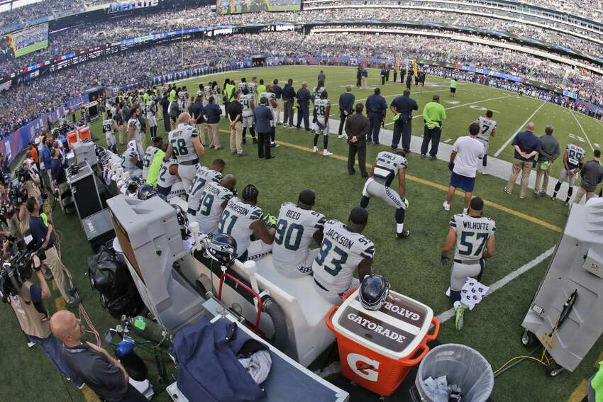 Some Seattle Seahawks sit or kneel during the national anthem before an NFL football game against the New York Giants, Sunday, Oct. 22, 2017, in East Rutherford, N.J. (AP Photo/Julio Cortez)