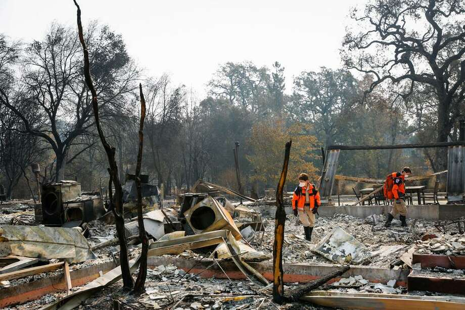Claudia Langley (left) and Liam Ferguson of Contra Costa Search and Rescue survey a property off Highway 12 in Glen Ellen on Wednesday. Residents were cleared Sunday to return to their neighborhoods in the small Sonoma County town. Photo: Gabrielle Lurie / The Chronicle / Gabrielle Lurie / The Chronicle