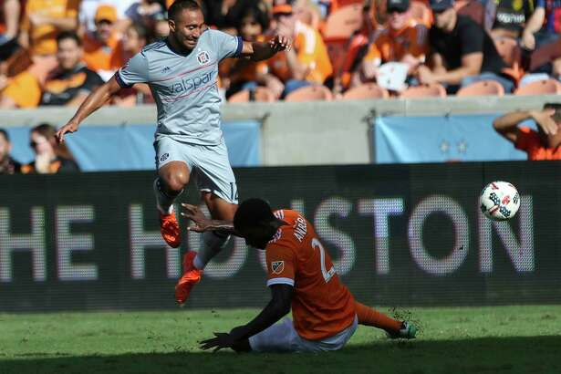 Chicago Fire forward Arturo Alvarez (12) leaps over Houston Dynamo defender Jalil Anibaba (2) while carrying the ball toward the box as Anibaba is trying to get the ball away from him during the first half of the last MLS regular game at BBVA Compass Stadiujm on Sunday, Oct. 22, 2017, in Houston.