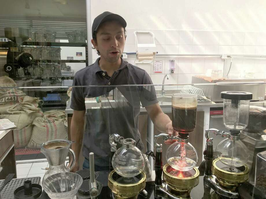 A barista at Varietale, a hip coffee house that opened in Bogota in 2015, brews coffee using the syphon method. The shop is one of many that have sprouted up amid a coffee drinking revolution. / Anthony Faiola, The Washington Post
