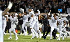 The Oakland Raiders team celebrates their 31-30 win over the Kansas City Chiefs during Thursday's football game at Oakland-Alameda County Coliseum on Oct. 19, 2017 in Oakland, Calif. (John Sleezer/Kansas City Star/TNS)