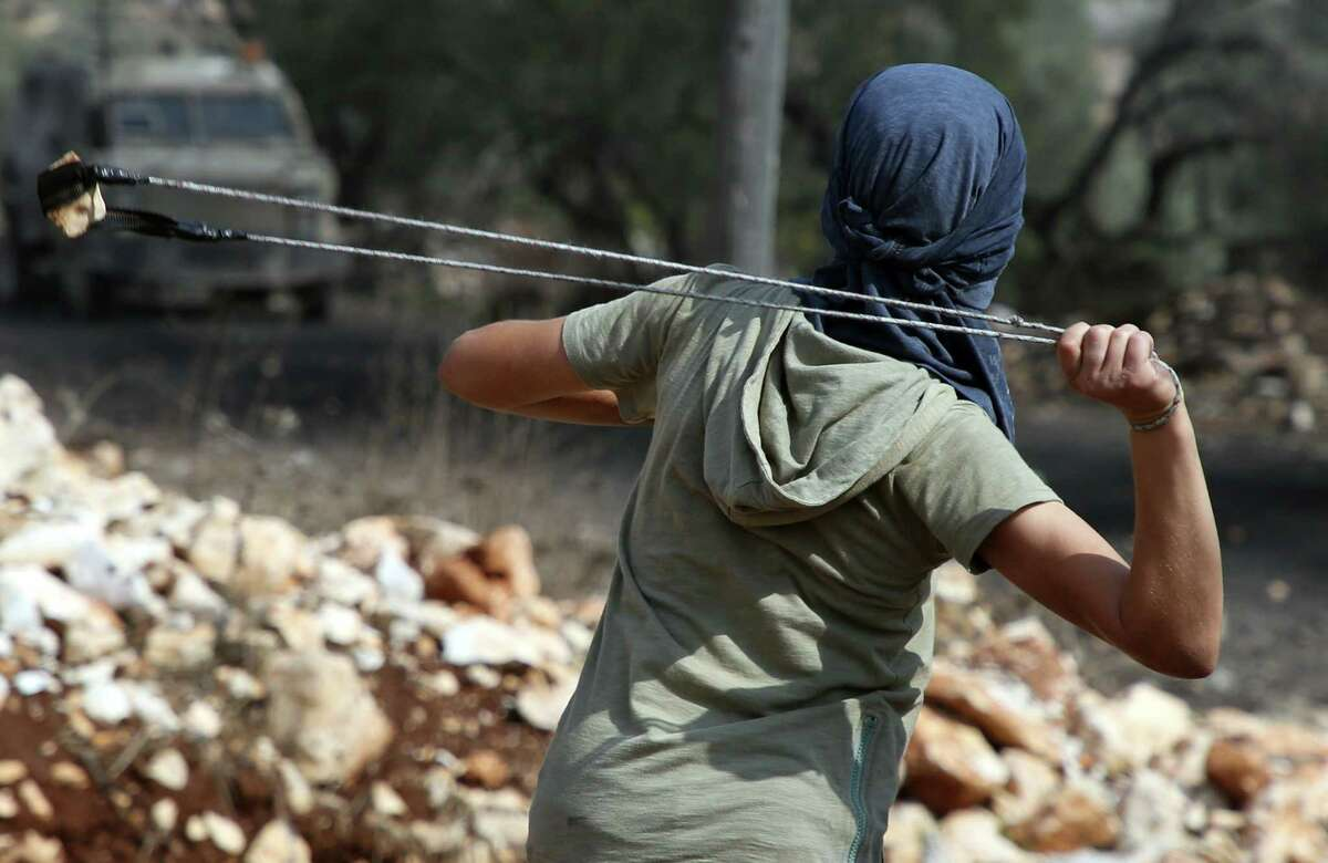 A Palestinian demonstrator uses his slingshot during clashes with Israeli forces following a weekly demonstration against the expropriation of Palestinian land by Israel in the village of Kfar Qaddum, near Nablus in the occupied West Bank on October 20. (Getty Images)