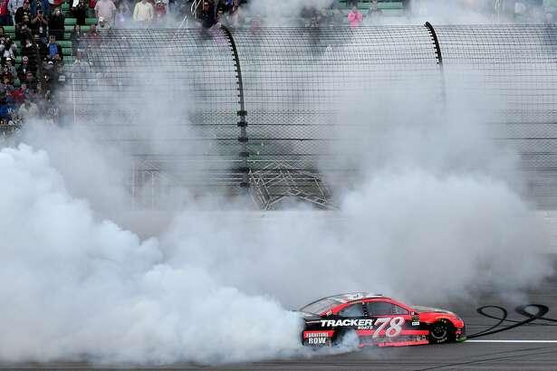 Martin Truex Jr. does a burnout after winning a NASCAR Cup Series auto race at Kansas Speedway Sunday, Oct. 22, 2017, in Kansas City, Kan. (AP Photo/Ed Zurga)