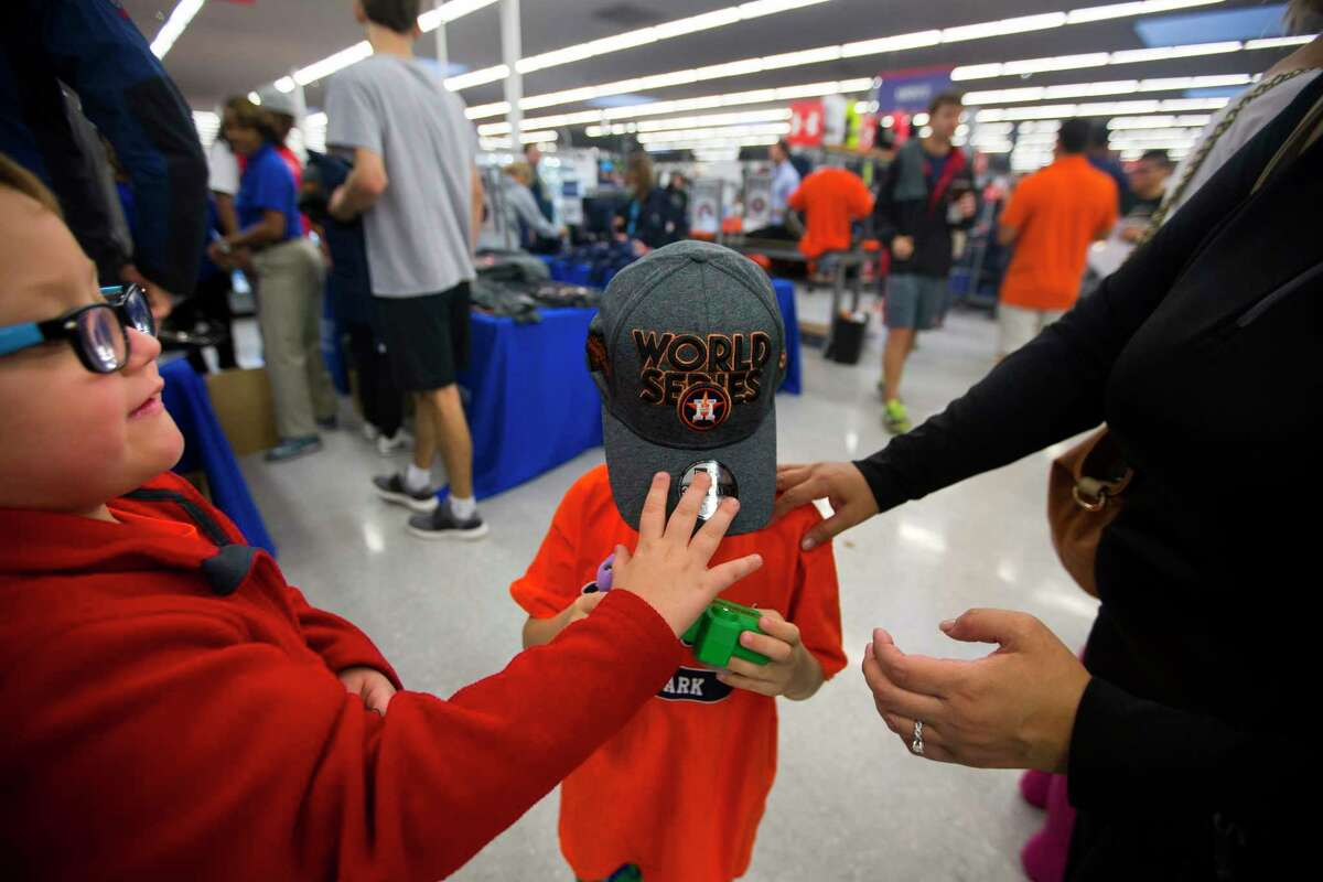 Young Astros fans try on the World Series hat at the Academy Sports + Outdoors location off of the Southwest Freeway on Sunday, Oct. 22, 2017, in Houston.