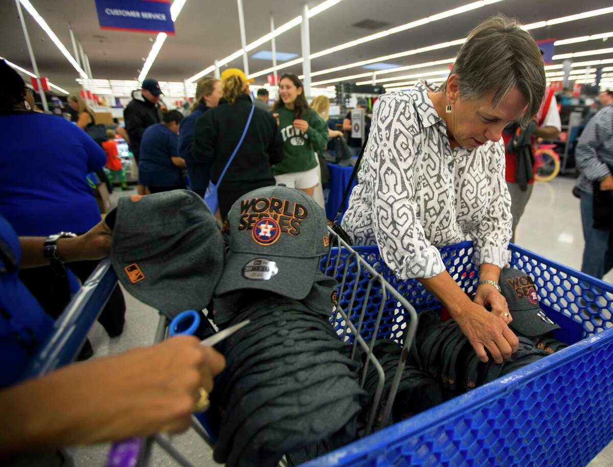 Cay Dickson, right, fills a shopping cart full of Astros World Series hats at the Academy Sports + Outdoors location off of the Southwest Freeway on Sunday, Oct. 22, 2017, in Houston. Dickson is helping plan an event for the American Board of Trial Advocates (ABOTA) and will be giving away hats to attendees.