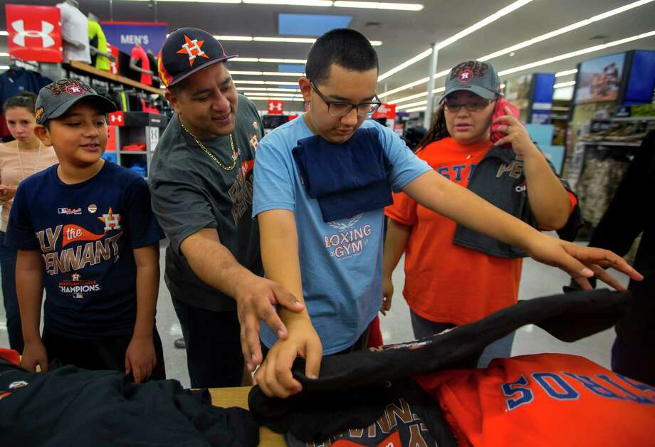 Armando Hercules, center, checks out Astros ALCS champion gear with his brother Antonio, left, and parents Carlos and Sandra at the Academy Sports + Outdoors location off of the Southwest Freeway on Sunday, Oct. 22, 2017, in Houston. The Hercules family has been awaiting a long time to see their beloved Astros in the World Series. Photo: Annie Mulligan / @ 2017 Annie Mulligan