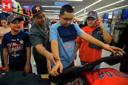 Armando Hercules, center, checks out Astros ALCS champion gear with his brother Antonio, left, and parents Carlos and Sandra at the Academy Sports + Outdoors location off of the Southwest Freeway on Sunday, Oct. 22, 2017, in Houston. The Hercules family has been awaiting a long time to see their beloved Astros in the World Series.