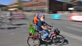 A three-wheeled cyclist turns onto the closed Broadway Street Sunday during the YMCA's semi annual siclovia event.
