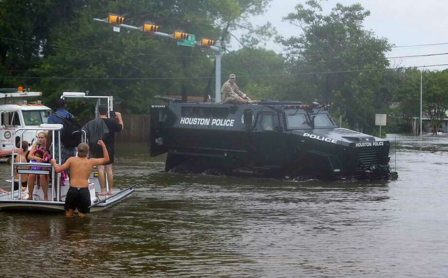 Members of the Houston Police Department ride in a department-owned MRAP through the flooded intersection of W. Belfort and Runnymeade in Meyerland, Sunday, Aug. 27, 2017, in Houston. (Mark Mulligan / Houston Chronicle) Photo: Mark Mulligan, Staff Photographer / 2017 Mark Mulligan / Houston Chronicle