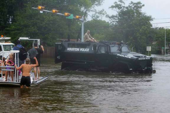 Members of the Houston Police Department ride in a department-owned MRAP through the flooded intersection of W. Belfort and Runnymeade in Meyerland, Sunday, Aug. 27, 2017, in Houston. (Mark Mulligan / Houston Chronicle)