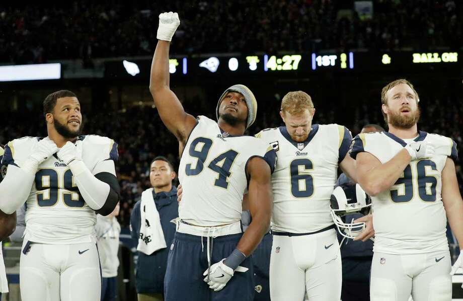 Rams outside linebacker Robert Quinn raises his fist during the playing of the national anthem as punter Johnny Hekker (6) bows in observance of the song before Sunday's game against the Cardinals in London. Photo: Matt Dunham, STF / Copyright 2017 The Associated Press. All rights reserved.